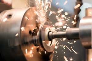 finishing metal working on lathe grinder machine with flying sparks